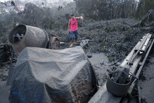 A man walks along ash fall covered plants and equipment as Taal Volcano continues to spew ash on Monday.