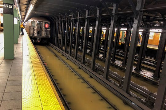 A subway train sits on flooded tracks at 66th Street, Monday, Jan. 13, 2020, in New York. A water main break flooded streets on Manhattan's Upper West Side near Lincoln Center and hampered subway service during the Monday morning rush hour.