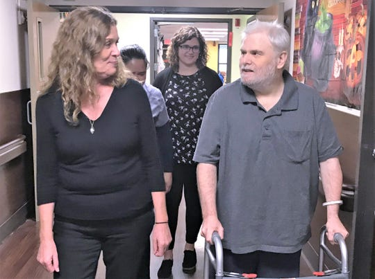 Karen Adams, a physical therapy assistant at the Corning Center for Rehabilitation and Healthcare, walks with James Duquette, who was successfully treated at the center for long term schizophrenia.
