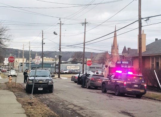 Several police cars gather near the intersection of First Street and College Avenue in Elmira on Monday afternoon after two suspects fled on foot during a traffic stop.