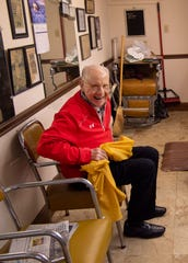 George Henson, 90, hops out of his chair at VIP Barber Shop as a customer walks in the door for a haircut Saturday morning, Jan. 11, 2020. Henson spent his usual half-day of work cutting hair before celebrating at two different birthday parties for him later in the day.