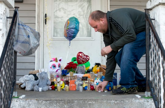 Kenny Branson, neighbor of slain Evansville 3-month-old Kieran Bengert, places tea lights around a memorial built on the porch of 1321 E. Illinois St. in preparation for a candlelight vigil being held Monday evening, Jan. 13, 2020.