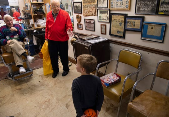 George Henson, center, points out the box full of suckers for Warner Kappler, 3, after finishing up Jay Picking's haircut at VIP Barber Shop Saturday morning, Jan. 11, 2020.