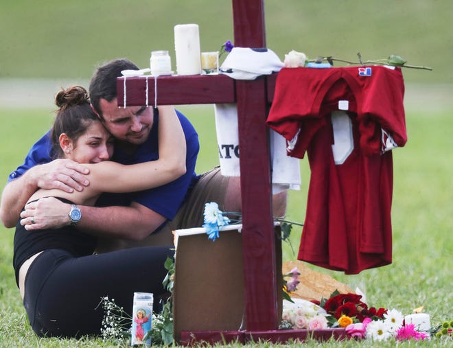 "Mourners gather at a cross for a student killed in the 2018 mass shooting at Marjory Stoneman Douglas High School, in Parkland. Before her election, U.S. Rep. Marjorie Taylor Greene confronted a Parkland survivor and called him a ""coward."""