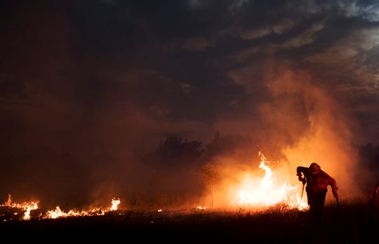 In this file photo, John Goodwin from the Florida Division of Forestry fights a brush fire off of State Road 82 near 40th Street in Lehigh Acres.
