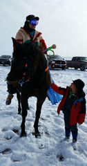 Terrance LaFromboise's son, Iisiikaatoyii (or Blacktail), looks up at Karl Ingraham on horseback for a healing ride to commemorate the Baker Massacre.