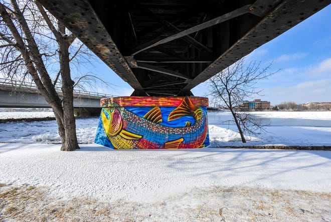 Ice builds up on the Missouri River under the Central Avenue West Bridge and pedestrian bridge causing the river to top the retaining wall in certain sections, Monday.