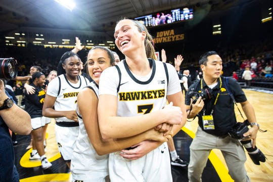 Iowa guard Makenzie Meyer, center, is embraced by teammate Gabbie Marshall as Hawkeyes players celebrate after defeating Indiana during a NCAA Big Ten Conference women's basketball game, Sunday, Jan. 12, 2020, at Carver-Hawkeye Arena in Iowa City, Iowa.