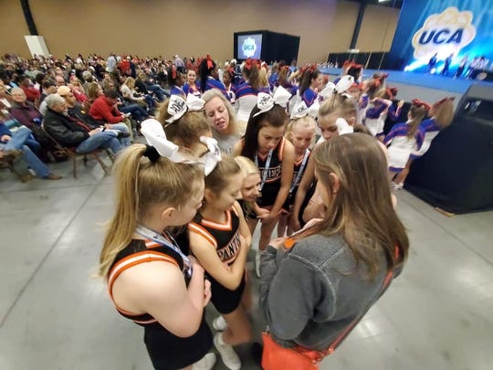 During the 2019 regional competition, Powell Middle School cheerleaders talk things over in a huddle.