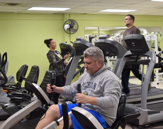Benji Bornino exercises at the Olivedale Park Health and Fitness Center while Ashlee Peters talks to Nick Hoover Thursday, Jan. 9. The center caters to adults 35 and up, offering classes and equipment.