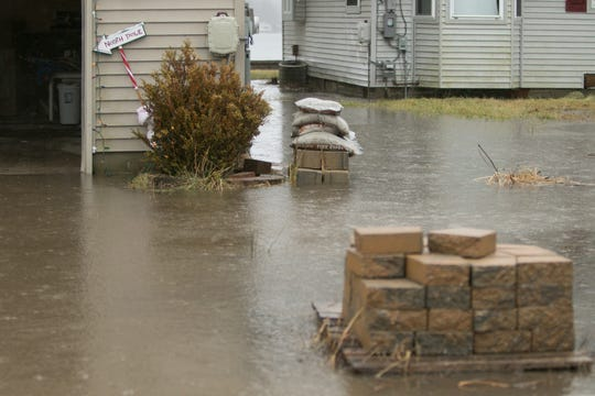 A pallet holding landscaping stones is partially obscured by floodwater in the driveway of 8000 Branch Drive in Hamburg Township Saturday, Jan. 11, 2020 as heavy rain fell in the area.
