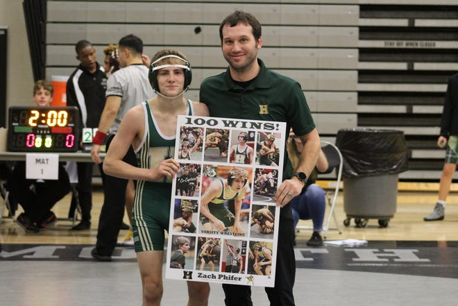 Howell's Zach Phifer poses with coach Quinn Guernsey after winning his 100th career wrestling match on Saturday, Jan. 11, 2020 in Plymouth.