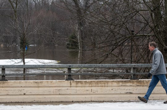 A pedestrian walks across the bridge on M-43 in downtown Williamston Monday, Jan. 13, 2020, where flooding from the Red Cedar river can be seen over parts of the Brookshire Inn & Golf Club's course.