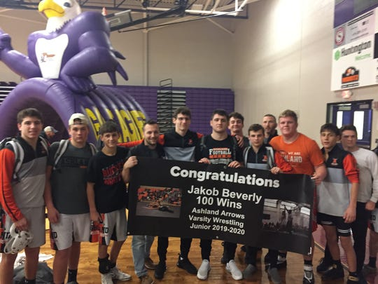 Ashland's Jakob Beverly is surrounded by teammates after collecting his 100th-career win.