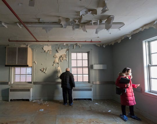 Geoff Hurtado, left, University of Wisconsin-Milwaukee associate vice chancellor, facilities planning and management, and Karen Wolfert, senior facilities architect, are shown in a room damaged by a steam leak in the building A complex of the former Columbia Hospital on Friday. The university purchased the complex in 2010 and is seeking to demolish the building A complex.