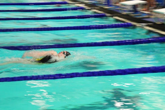 Central Magnet's Kailey Orr competes in the girls 100 backstroke at the county swim meet Sunday.