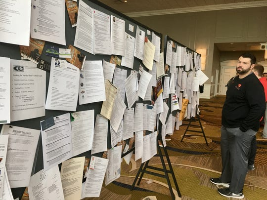 Prospective coaches post their resumes on large bulletin boards during the American Football Coaches Association convention at Opryland Hotel and Convention Center.