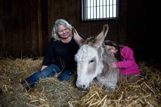 Sally Shaffer and her granddaughter, Aubrey, sit with one of the animals she has rescued and houses at her stable in Thornville. Daisy, Shaffer says, is sweet, but has bad feet and trouble standing. Her granddaughter, Aubrey, loves to sit with her.