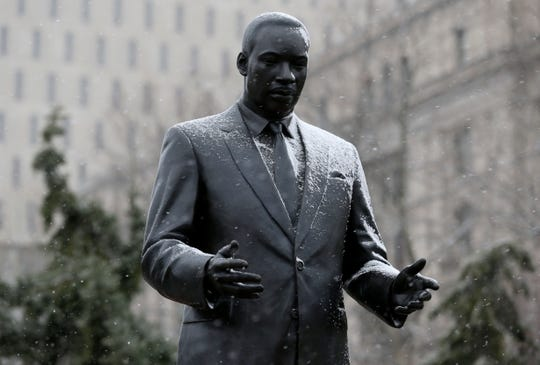 A light during of snow falls on a statue of Martine Luther King Jr. in Newark, N.J., Sunday, Jan. 17, 2016.