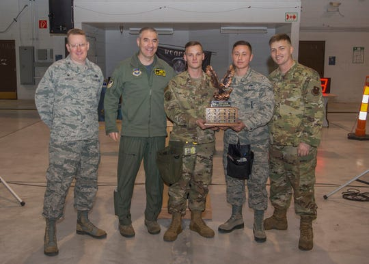 Col. Joseph Campo, 49th Wing commander (second from left), and Col. Tim Harbor, 49th Maintenance Group commander, present the first place trophy to weapons load crew members from the 314th Fighter Squadron during the fourth quarter load competition awards ceremony, Jan. 10, 2020, on Holloman Air Force Base, N.M. 12 Airmen from the 9th Aircraft Maintenance Unit, 29th AMU, 314th FS and 311th FS competed to see who could load munitions onto their respective aircraft the fastest.