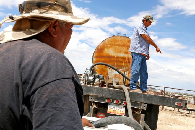 At left, Richard Root and Melvin Jones, both equipment operators for the Shiprock Chapter house, deliver water to a residence in Shiprock for livestock usage on Aug. 11, 2015.