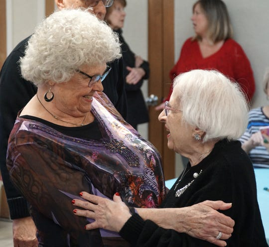 Alice Hosback, right, greets Eleanor Malone at her 100th birthday party.