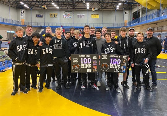 South Lyon East wrestlers Matthew Cepak and AJ Garcia celebrate their 100th career wins on the mat.