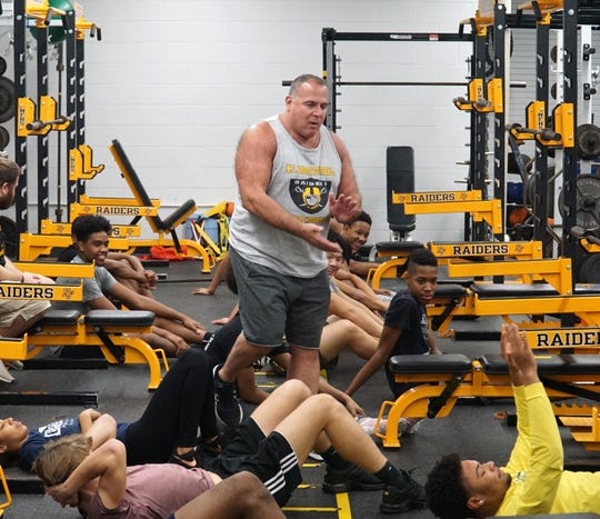 North Farmington High weightlifting coach Billy Slobin, center, starts a session for athletes on Jan. 13, 2020.