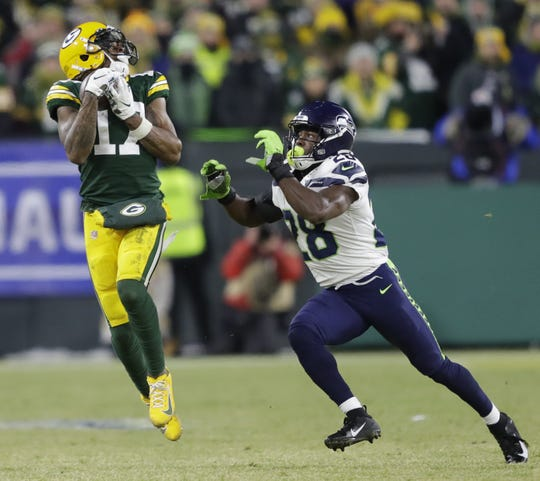 Green Bay Packers wide receiver Davante Adams (17) pulls down a first down reception on third down against Seattle Seahawks cornerback Ugo Amadi (28) late in the fourth quarter during their NFC divisional round playoff football game Sunday, January 12, 2020, at Lambeau Field in Green Bay, Wis.