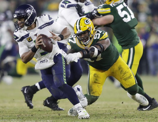 Green Bay Packers nose tackle Kenny Clark (97) pressures Seattle Seahawks quarterback Russell Wilson (3) in the first half during their NFC divisional round playoff football game Sunday, January 12, 2020, at Lambeau Field in Green Bay, Wis.