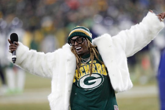 Recording artist Lil Wayne addresses the crowd in the second half of a NFC Divisional Round playoff football game between the Green Bay Packers and Seattle Seahawks at Lambeau Field.