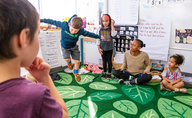Students finish up their morning circle time at Phoenix Modern charter school on Wednesday, October 30, 2019.  From left to right are students Troy Myers, 5, William Lavicka, 6, Evangeline Dailey, 7, guide (teacher) BreeAnna Grissum and student Sabria Baker, 4.
