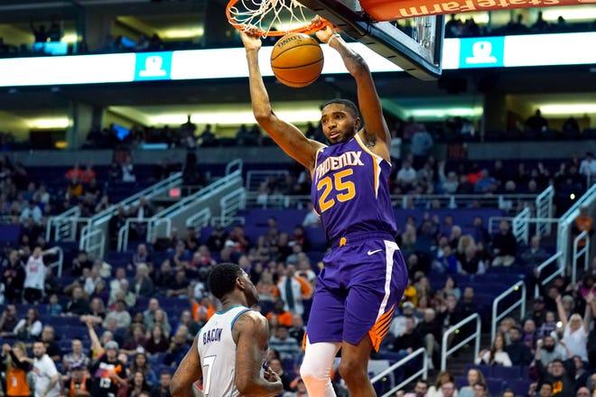Phoenix Suns forward Mikal Bridges dunks over Charlotte Hornets guard Dwayne Bacon (7) during the second half of an NBA basketball game Sunday, Jan. 12, 2020, in Phoenix. Phoenix won 100-92. (AP Photo/Rick Scuteri)