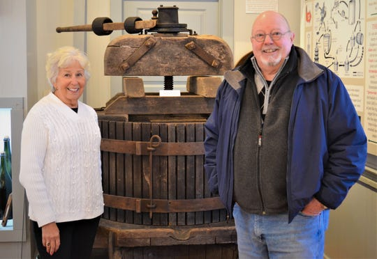 Jane Spriestersbach and Craig Koerpel stand next to a vintage wine press at the Catawba Museum at Union Chapel.