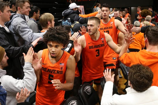 Oregon State's Ethan Thompson (5), Tres Tinkle (3) and Roman Silva celebrate their 82-65 win over Arizona with fans after an NCAA college basketball game in Corvallis, Ore., Sunday, Jan. 12, 2020.