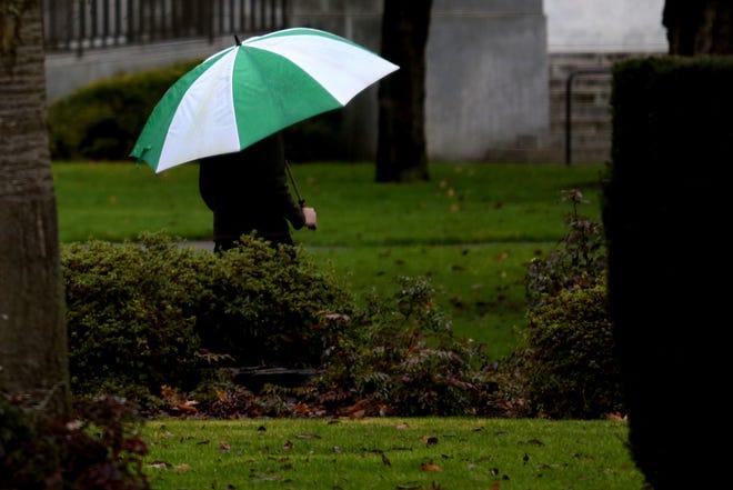 A person walks as rain falls in Salem on Jan. 13, 2020.