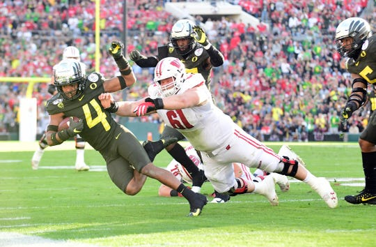 Jan 1, 2020; Pasadena, California, USA; Oregon Ducks cornerback Thomas Graham Jr. (4) is tackled by Wisconsin Badgers offensive lineman Tyler Biadasz (61) after intercepting a pass against in the second quarter during the 106th Rose Bowl game at Rose Bowl Stadium. Mandatory Credit: Gary A. Vasquez-USA TODAY Sports