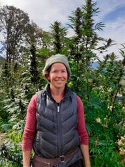Dove Oldham poses in front of a hemp plant growing at Madrona Family Farm in Grants Pass.