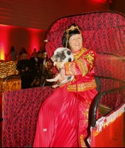 """Artemis-Springhill  2020 Captain Donna Waring holds a squealing pig as part    of the Grand Bal Tableau. The theme: """"L'Orient-Artemis Style."""""""