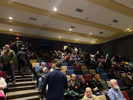 People begin to fill the Kate Collins Middle School auditorium. About 400 people filled the auditorium by 7 p.m.
