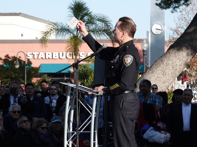 Oxnard Police Chief Scott Whitney holds up a card promoting community service at the interfaith Oxnard Together event at Plaza Park in January 2020.