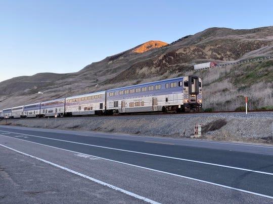 An Amtrak Pacific Surfliner train travels along Pacific Coast Highway north of Ventura.