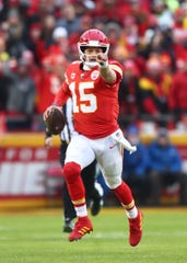 Kansas City Chiefs quarterback Patrick Mahomes (15) points as he runs the ball against the Houston Texans in the first half of the AFC Divisional Round playoff football game at Arrowhead Stadium.