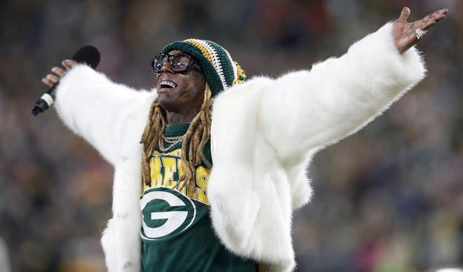 Recording artist Lil Wayne addresses the Lambeau Field crowd at the NFC Divisional game against the Seattle Seahawks last year.