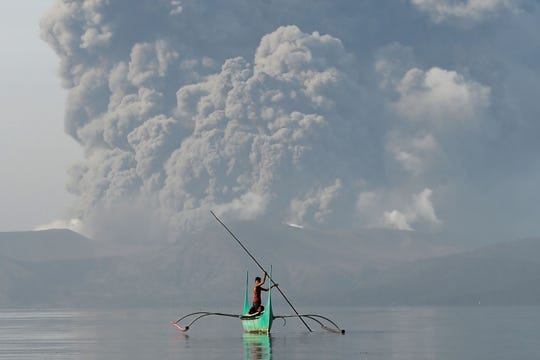 A youth living at the foot of Taal volcano rides an outrigger canoe while the volcano spews ash as seen from Tanauan town in Batangas province, south of Manila, on Jan. 13, 2020.