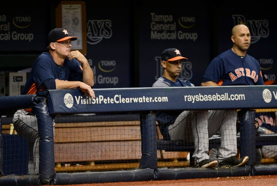 Manager A.J. Hinch, former bench coach Alex Cora and then-outfielder Carlos Beltran watch from the visitors dugout as the Astros play the Rays in 2017. All three are central figures in MLB's report on the Astros' sign-stealing scandal.