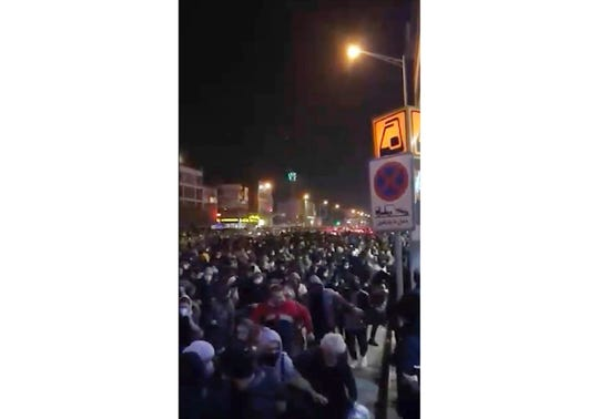 This image from a Jan. 12, 2020, video provided by the New York-based Center for Human Rights in Iran shows people fleeing police near Azadi, or Freedom, Square in Tehran.