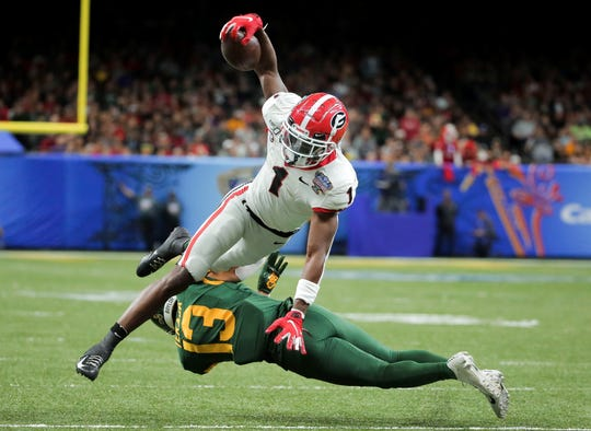 Georgia wide receiver George Pickens  leaps over Baylor  cornerback Raleigh Texada during the second quarter of the 2020 Sugar Bowl.