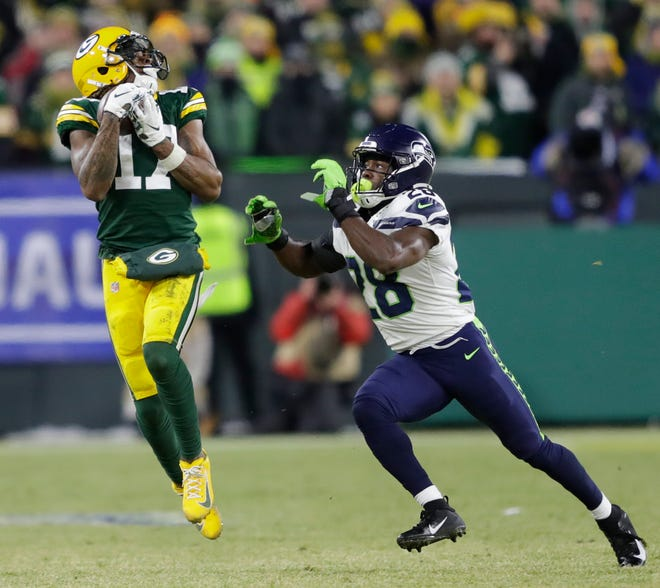 Green Bay Packers wide receiver Davante Adams (17) pulls down a first down reception on third down against Seattle Seahawks cornerback Ugo Amadi (28) late in the fourth quarter during their NFC divisional round playoff football game Sunday, Jan. 12, 2020, at Lambeau Field in Green Bay, Wis.