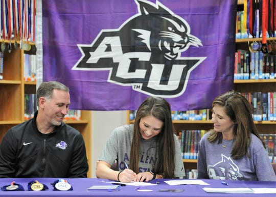 Flanked by dad Brit and mom Krista, Merkel senior Kaydi Pursley signs her letter of intent to the Abilene Christian track and field program at a ceremony Tuesday in the high school library.